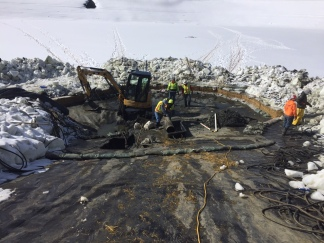 Workers build a dam around the site to control ice melt from saturating the work area
